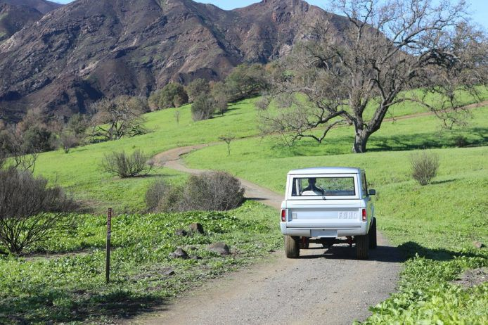 Bronco driving down road