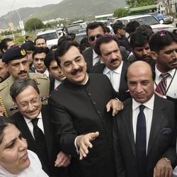 Pakistani Prime Minister Yousuf Raza Gilani, center, makes his way to the Supreme Court for a hearing in Islamabad, Pakistan, Thursday, April 26, 2012.  The Supreme Court convicted Gilani of contempt on Thursday for refusing to reopen an old corruption case against President Asif Ali Zardari on Thursday, but spared him a prison term in a case that has stoked political tensions in the country.