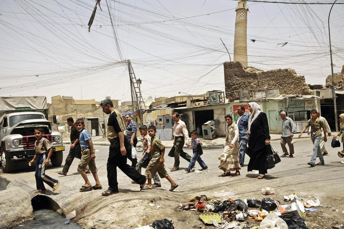 FILE - In this Monday, June 8, 2009 file photo, residents walk past the tilted minaret of al-Nuri mosque in busy market area in Mosul, Iraq. U.S.-backed Iraqi troops pushed into the last Islamic State stronghold in the country's second largest city of Mos