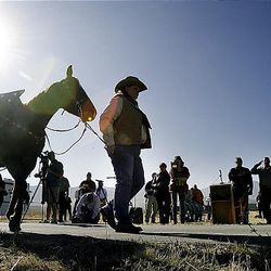 Marsha Milburn of the Salt Lake County Sheriff's Office leads a riderless horse past a grave marker for deputy James D. Hulsey, who was killed in the line of Duty in 1913. The ceremony was held Monday in the Bingham City Cemetery.