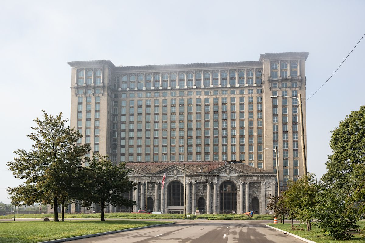 The exterior of Michigan Central Station in Detroit. The facade has multiple windows and columns flanking the entryway and lower level windows.