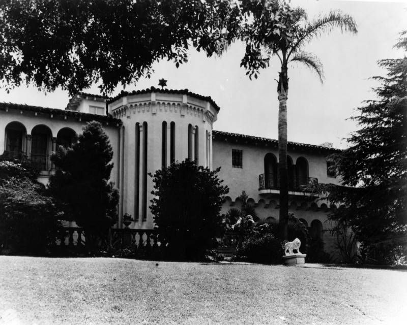 A large white building with a domed entrance. There are palm trees outside of the building.