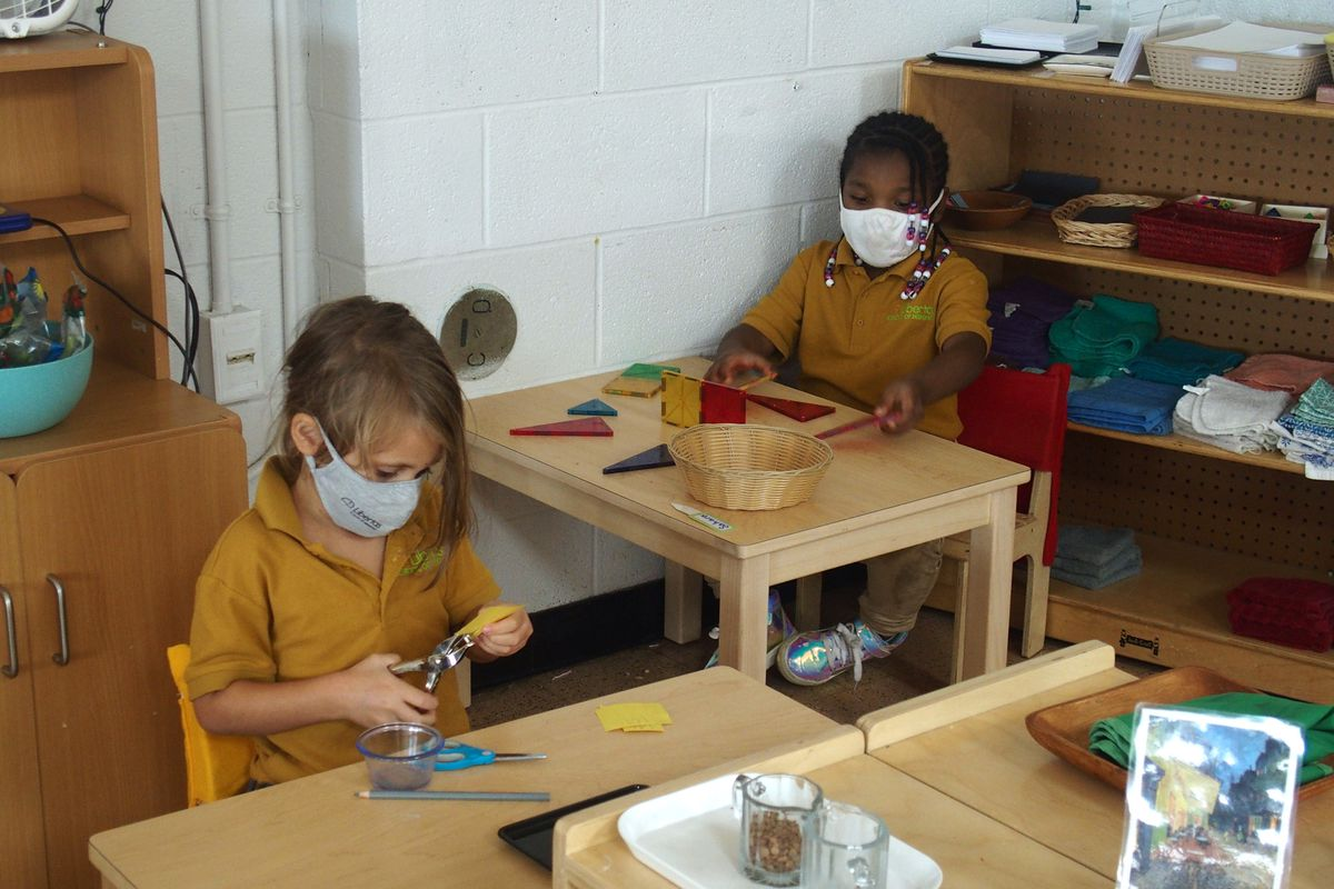 Elementary school students work at their desks with masks on