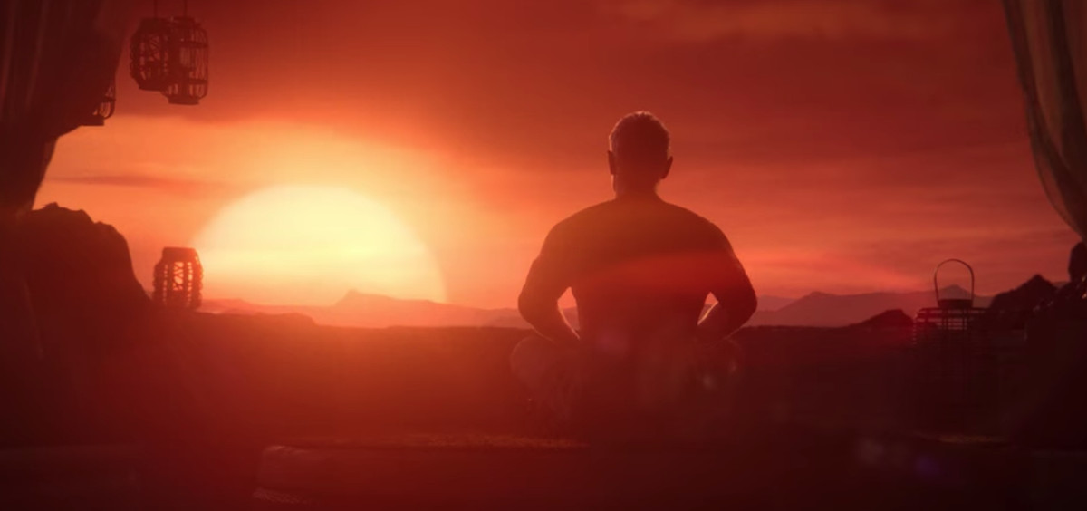 a man sitting crosslegged in front of the setting sun