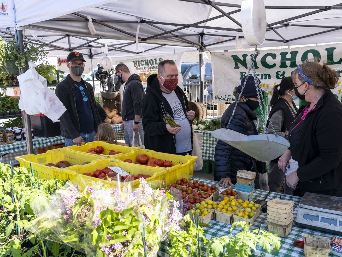 People grab produce and wait to check out at the Nichols Farm and Orchard stall at the Andersonville Farmers Market, Wednesday, May 12, 2021.