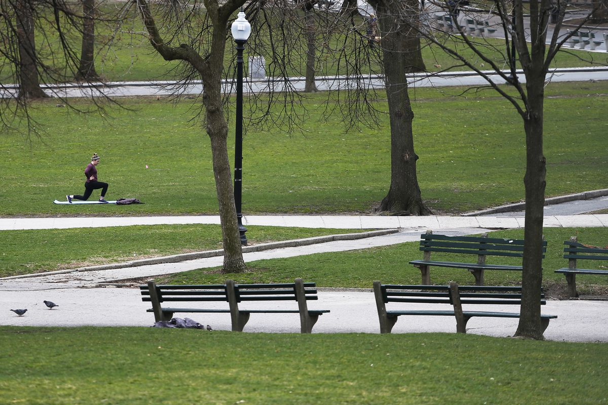 A lone woman in the distance exercising amid an otherwise empty park.