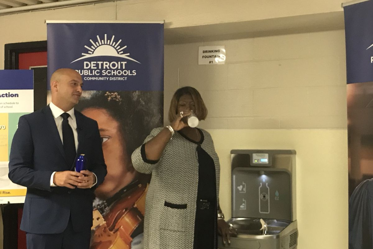 Superintendent Nikolai Vitti looks on as Iris Taylor, president of the Detroit school board, drinks from one of the more than 500 water hydration stations that have been installed in schools across the Detroit district.