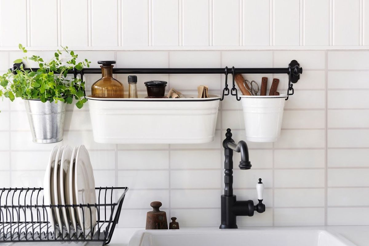 A kitchen has a deep white farmhouse sink, white dishes drying in a black rack, and white buckets hanging from a black bar behind the sink.