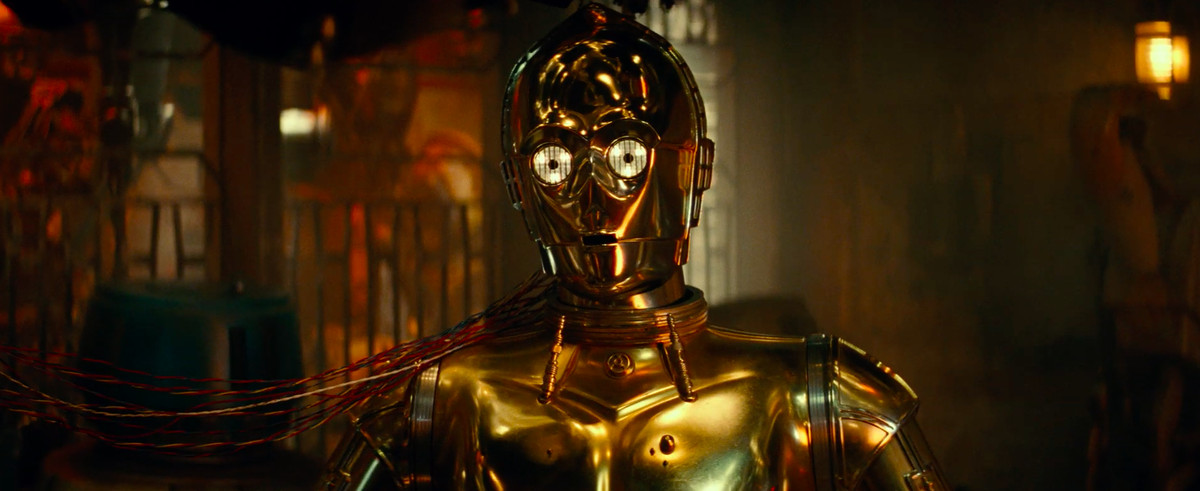 a battle droid hangs on the wall behind a plugged-in C-3PO
