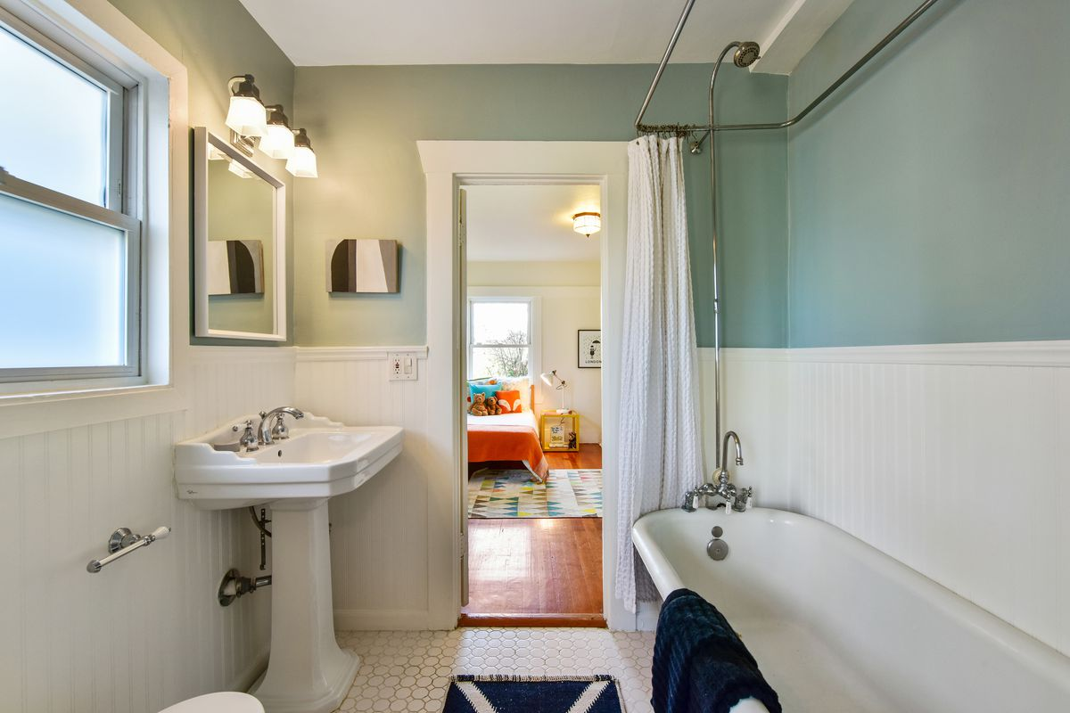 A bathroom with white pedestal sink, light green walls, and a clawfoot tub.