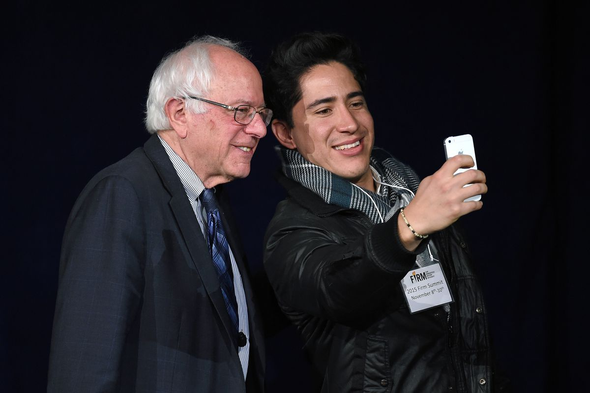 Bernie Sanders poses for a selfie with a fan.