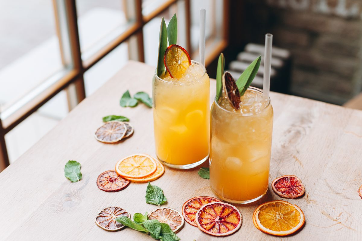 Two orange cocktails with dried citrus slices, green leaves, and straws on top of a white table cloth table with scattered dried citrus slices and green leaves