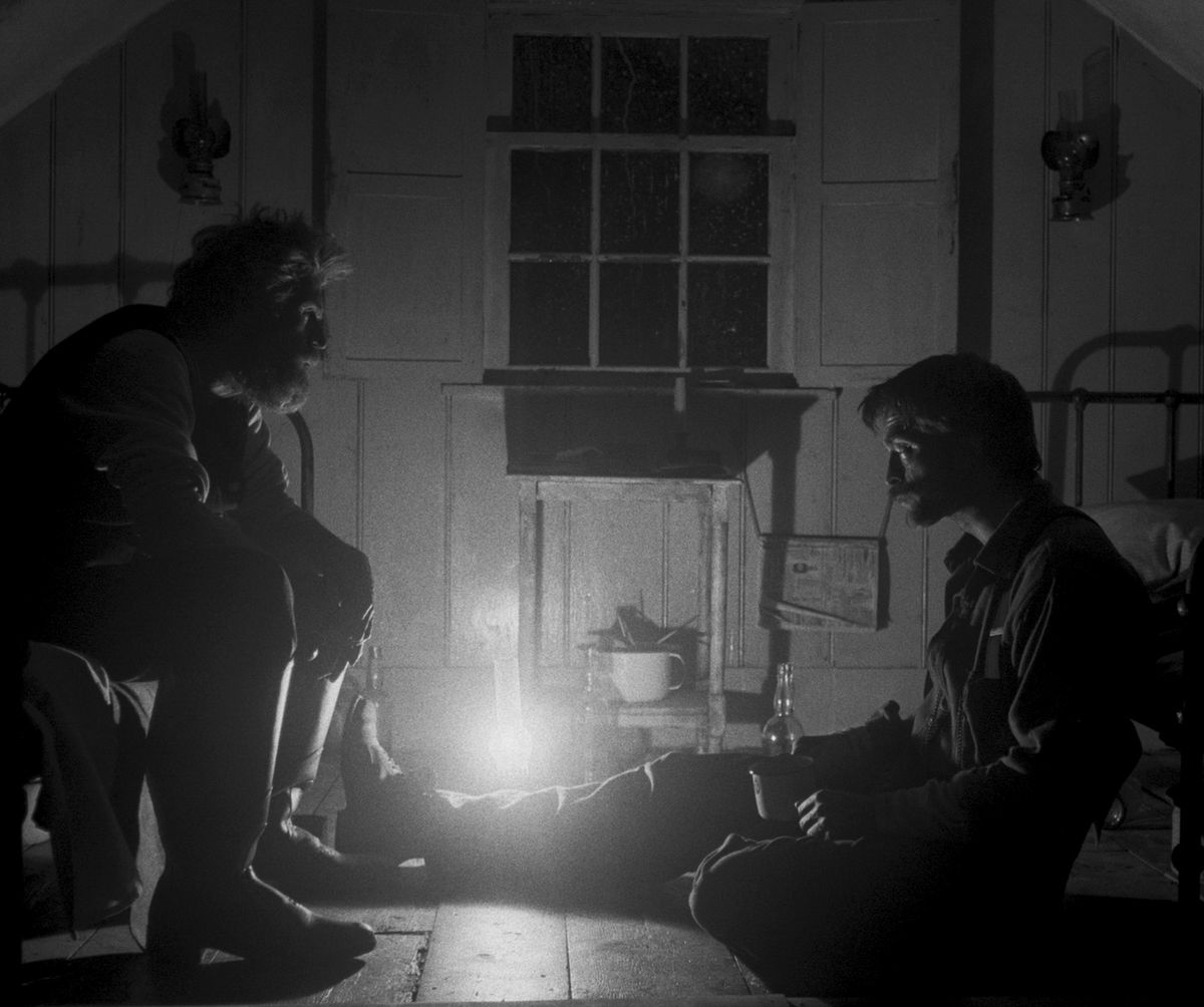 dafoe and pattinson sit across from each other on the floor, lit only by a oil lamp