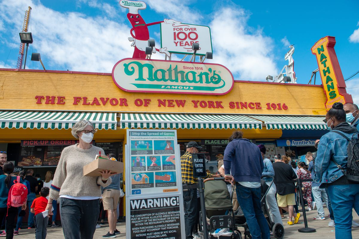 """People wait near a """"stop the spread of germs"""" sign at Nathans Famous at Coney Island on Memorial Day in the Brooklyn Borough of New York on May 31, 2021 in New York City. On May 19, coronavirus pandemic restrictions were lifted making Memorial Day the first holiday weekend without any restrictions in over 15 months. Much of the three-day holiday weekend was rained out with temperatures dropping to the 50s and 60s."""