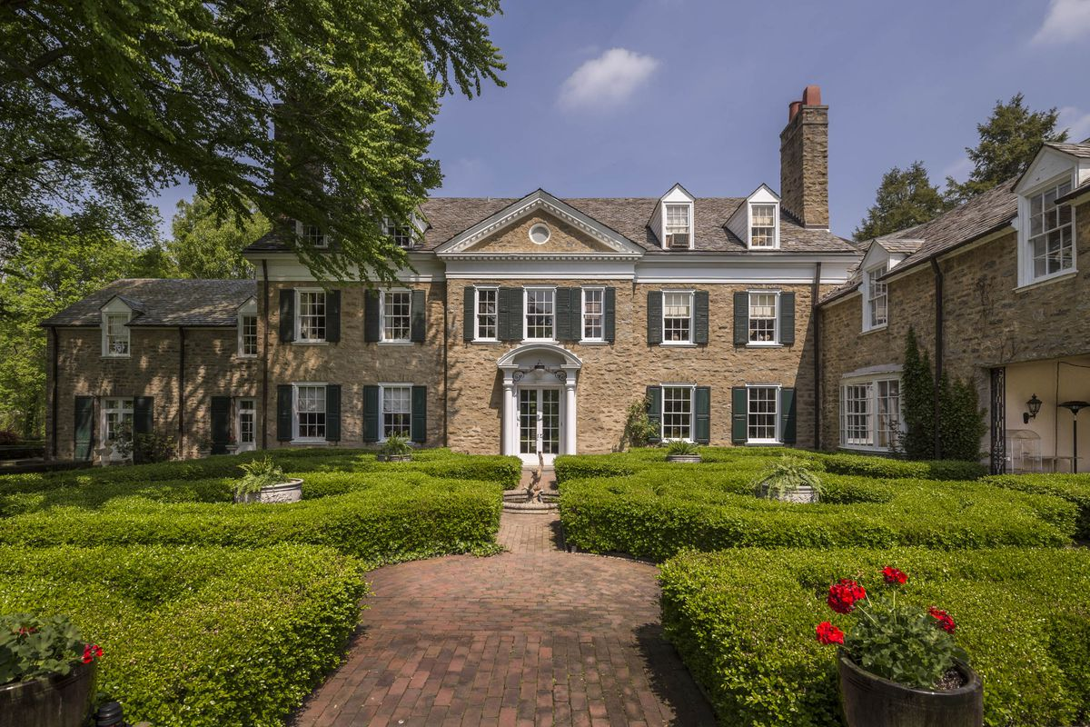 A stone mansion with landscaped formal gardens.