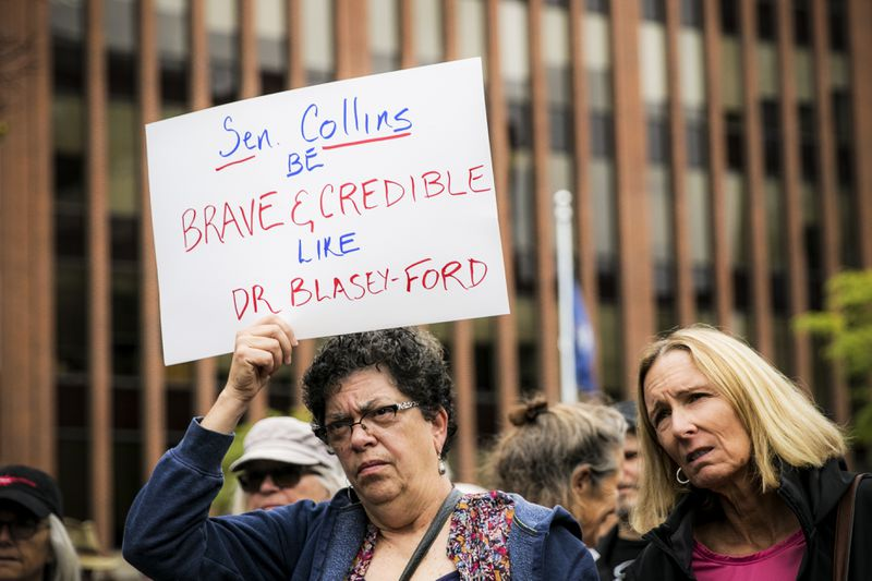 Yvonne Berry (left) and Wendy Keeler gather with protestors across the street from Sen. Susan Collins' office in Portland, Maine, to urge Sen. Collins to vote no on the confirmation of Supreme Court nominee Brett Kavanaugh on September 28, 2018.