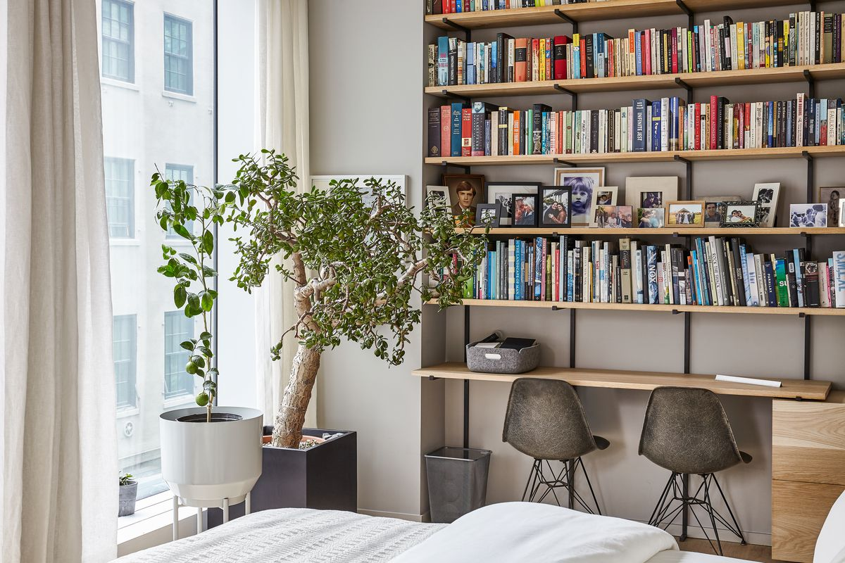 A living area with built-in wooden shelves that hold many books and assorted objects. There are plants in planters next to a floor to ceiling window. In the foreground is the corner of a bed with white bed linens.
