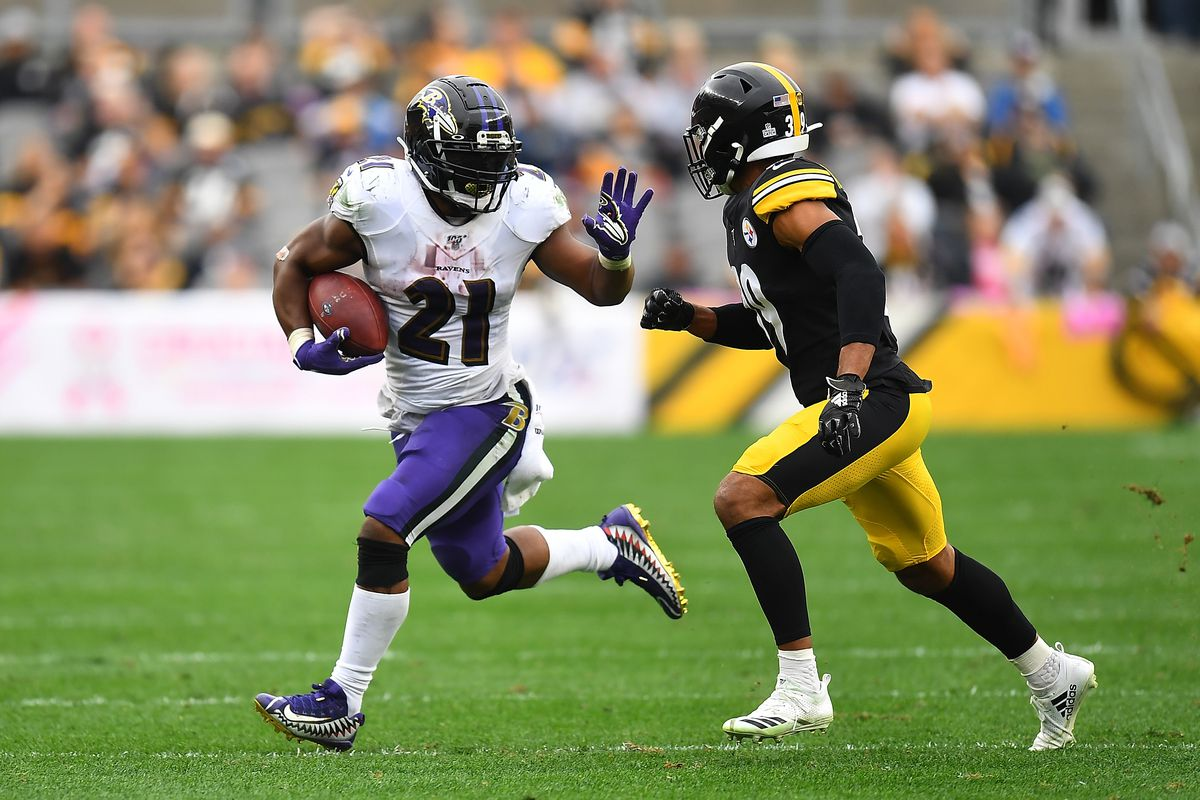 Mark Ingram of the Baltimore Ravens carries the ball in front of Minkah Fitzpatrick of the Pittsburgh Steelers during the second half at Heinz Field on October 6, 2019 in Pittsburgh, Pennsylvania.