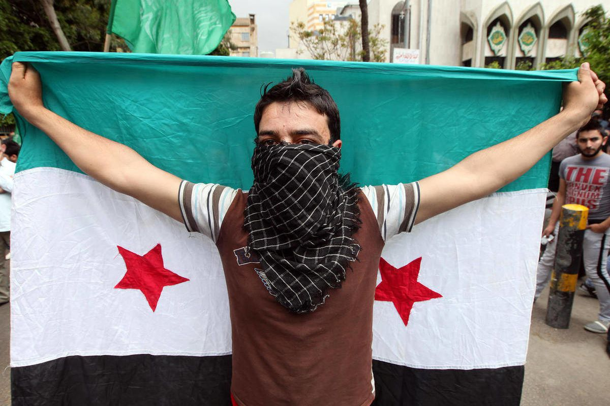 Supporter of an Islamic group, holds up a Syrian revolution flag, as he march during a demonstration against the Syrian regime, after Friday prayers, in Beirut, Lebanon, Friday, April 20, 2012.  The United Nations hopes to have 30 cease-fire monitors in S