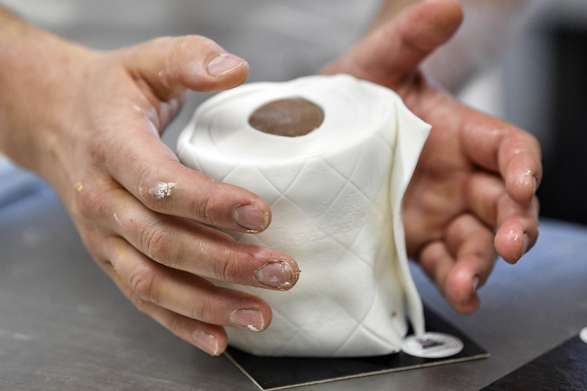 A baker forms round marble cakes wrapped in fondant that look like toilet paper rolls, as a funny comment to the toilet paper frenzy due to the coronavirus outbreak, in Dortmund, Germany, Thursday, March 26, 2020. The special cake became a local bestseller at the bakery. The new coronavirus causes mild or moderate symptoms for most people, but for some, especially older adults and people with existing health problems, it can cause more severe illness or death. (AP Photo/Martin Meissner)