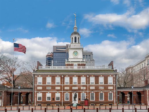 The exterior of Independence Hall in Philadelphia. The base of the building is red and there is a white tower.