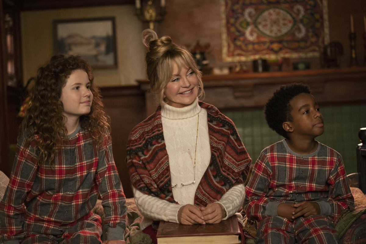 Goldie Hawn and the child cast of The Christmas Chronicles 2 sit in stiff poses wearing competing loud patterns