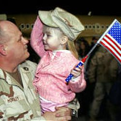 Sfc. Jay Horsley is greeted with a hug from his only granddaughter, Zoie, 4, as he returns from active duty.