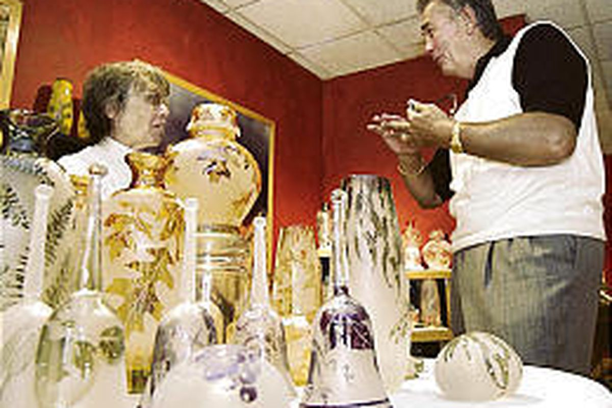 Kelsey Murphy, left, discusses the art of handblown glass with Marlin Grimwood at GlassWorks-WV.
