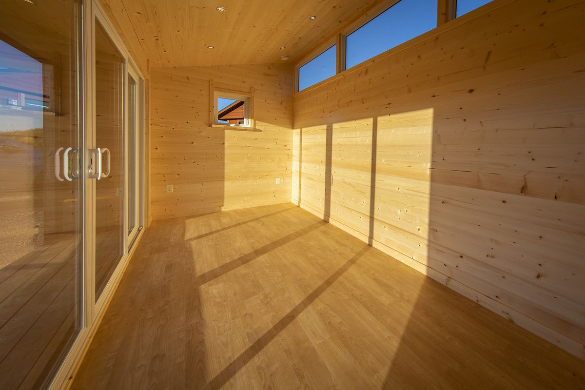 A wooden shed interior with glass doors and clerestory windows.