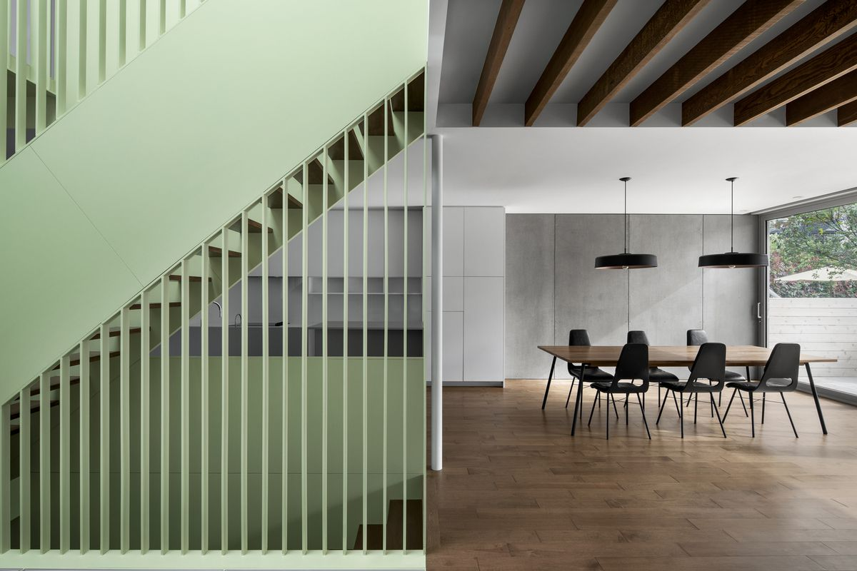 Dining area next to sage green staircase.