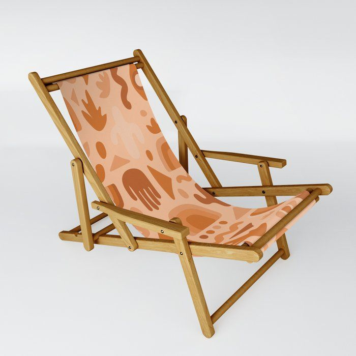 Wooden lounge chair with pink fabric seat.