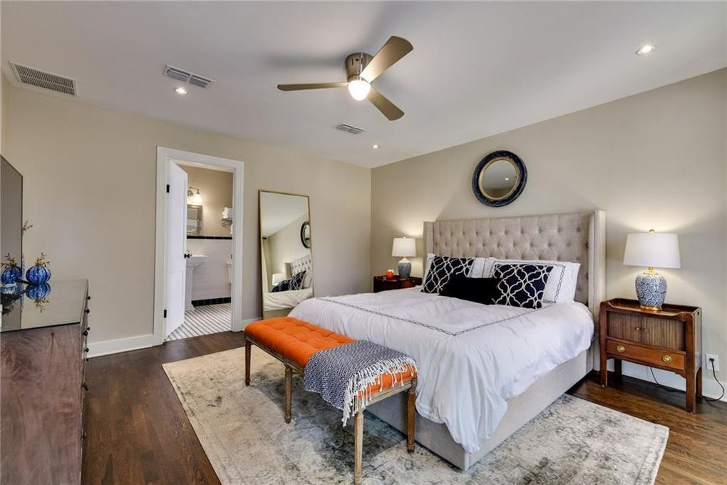 A bed with a linen tufted headboard and white bedding is pushed against one wall. There are to midcentury style end tables and an orange bench at the bottom of the bed. The walls are beige.
