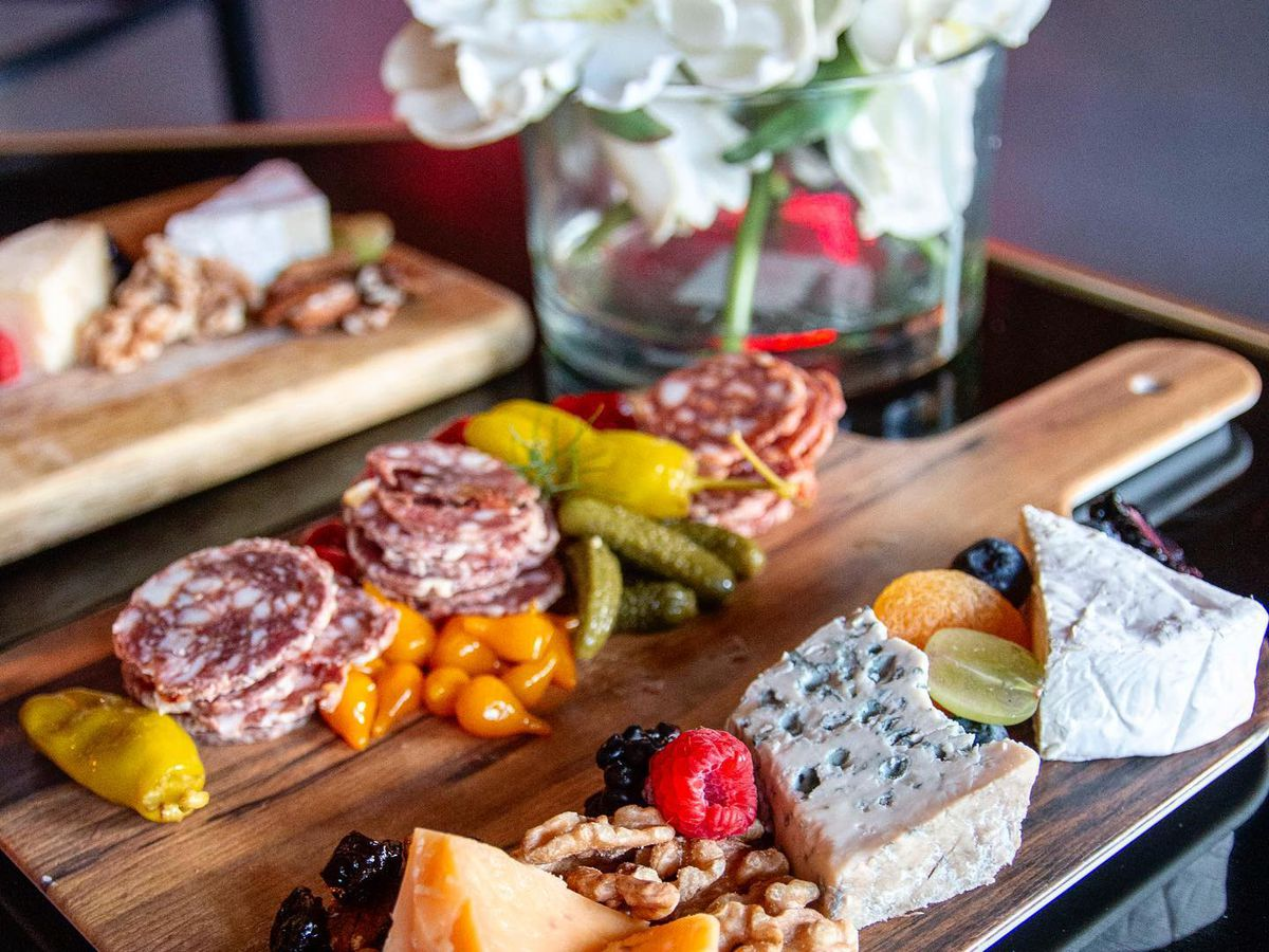 Two cheese boards and one charcuterie board on a table