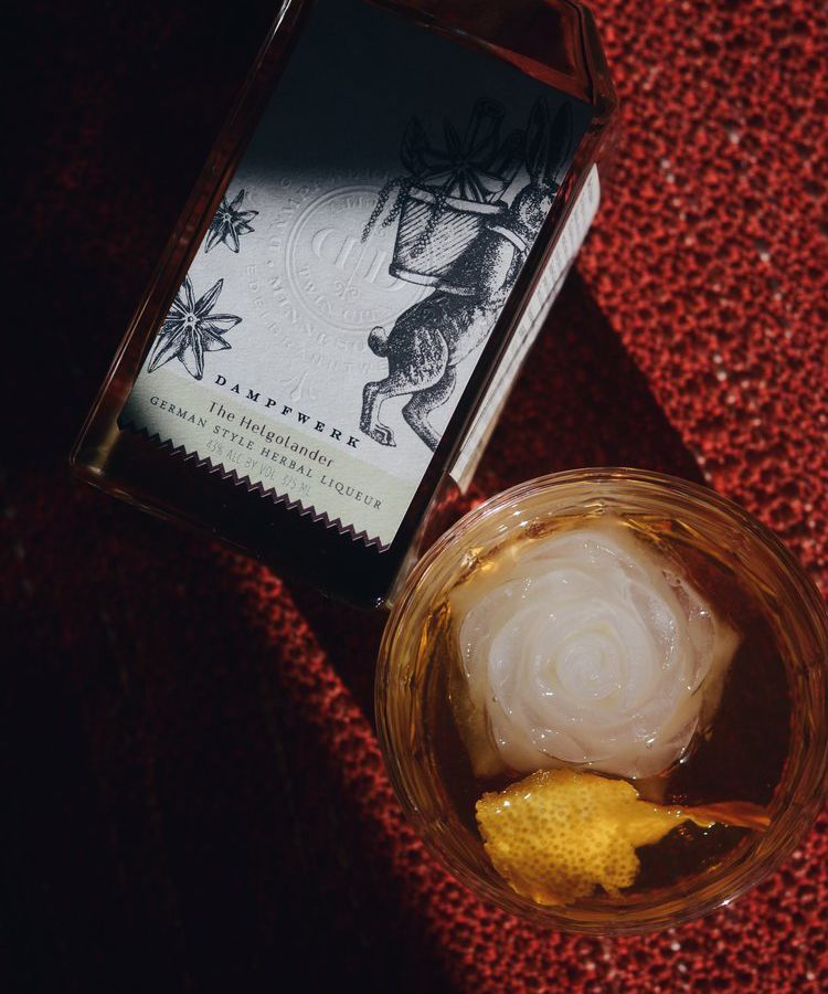 A bottle of Hegolander lays on a red sweater material next to a cocktail glass with a giant ball of ice, filled with brown liquid