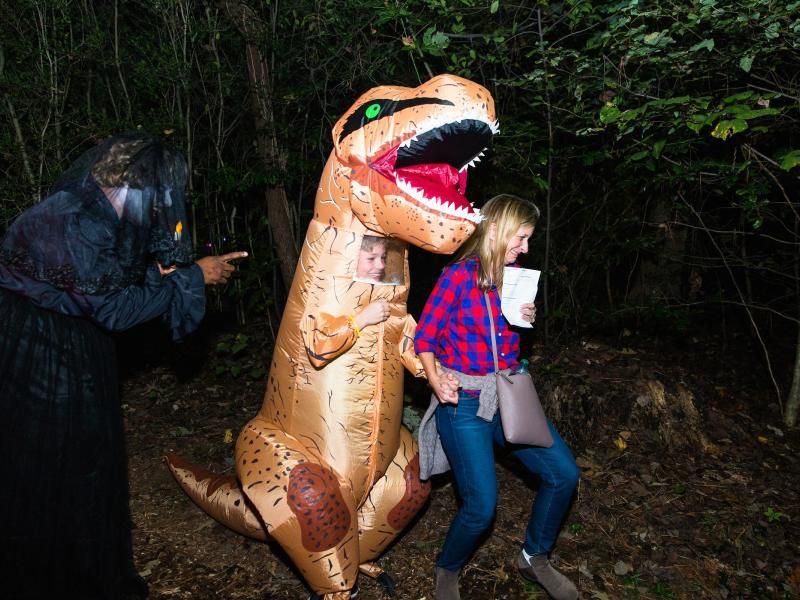 Someone dressed as a dinosaur scares a woman as another adult looks on.