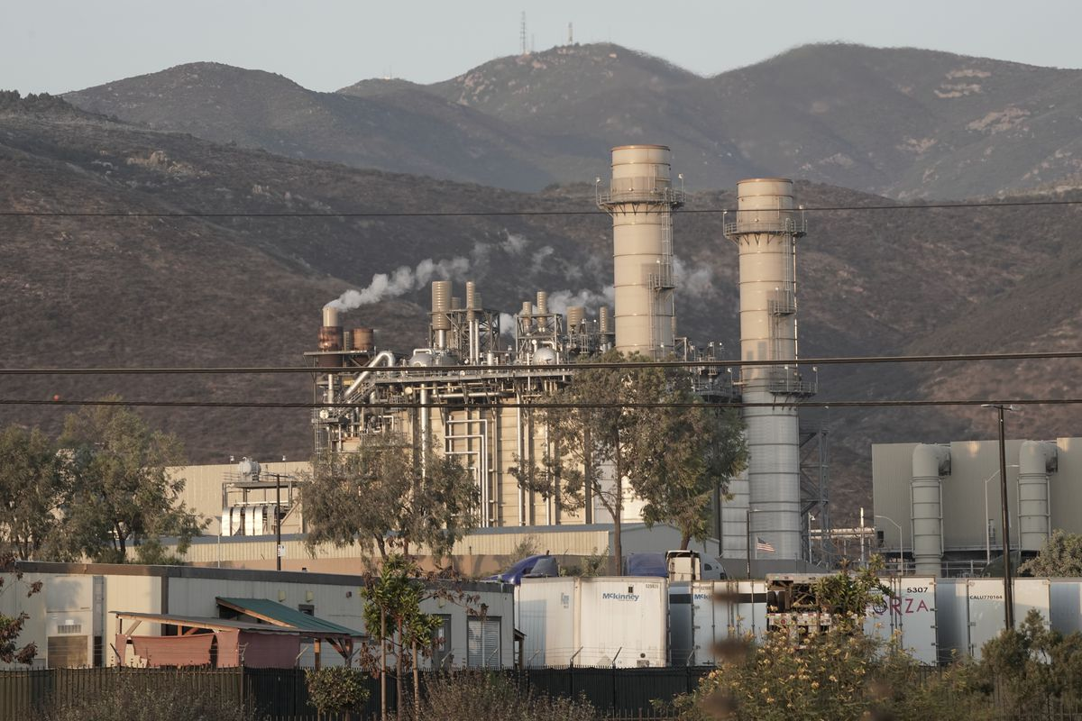 Amid rolling, verdant hills clothed in smog, sit two wide smoke stacks, positioned just to the right of thin metal towers and thinner smokestacks spewing fumes. A tangle of black wires run horizontally across the photo's foreground.