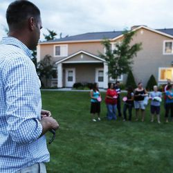 Bishop Steven Kippen speaks as friends gather during a candle light vigil in Logan Thursday, July 10, 2014. Ronald Lee Haskell, a recent Logan resident, has been charged with multiple counts of capital murder in a shooting in Texas. Haskell and his family lived in Logan for several years.