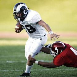 Highland High School's Bridger Walzer (left) tries to escape the grasp of East Highl's J.J. Fonua (right) in prep football action.