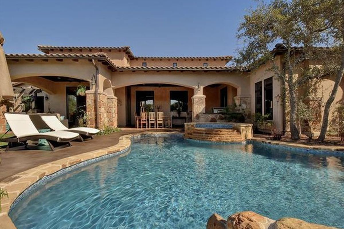 Large Spanish-style two-story with pool in front, stucco, red clay tile roof