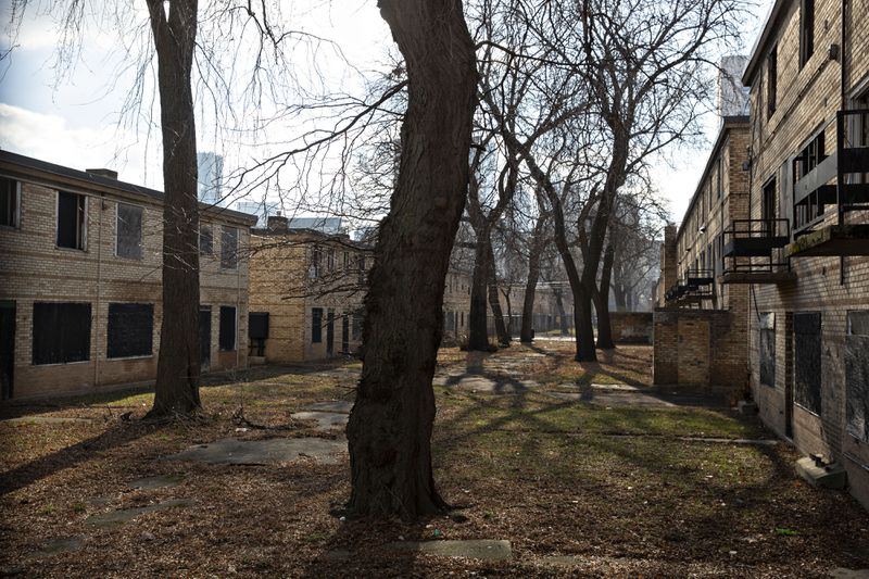 A line of abandoned yellow buildings in a deserted, tree-strewn housing complex.