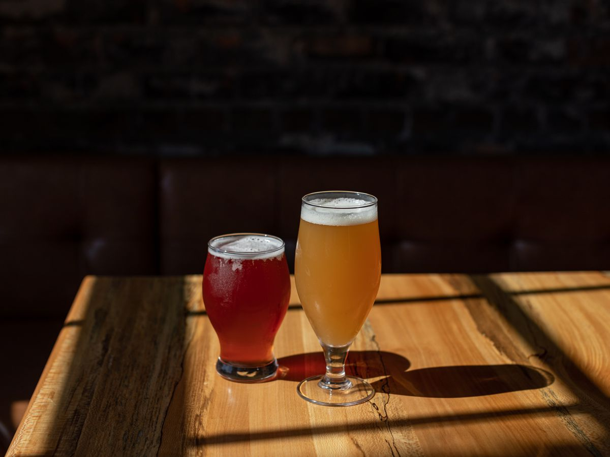 A reddish colored beer in a smaller glass stands next to a cloudy, amber colored beer in a taller glass.