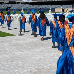 Graduates of Whitney M. Young Magnet High School proceed out to the floor of ceremony at Soldier Field on Wednesday afternoon.