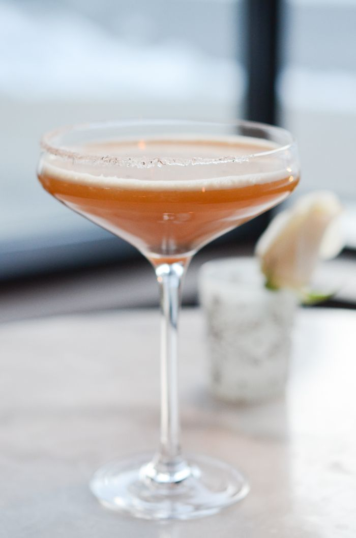 A close up on a particularly curvy, sexy tall coup class rimmed with a little sugar and a bourbon sort of cocktail is served up.