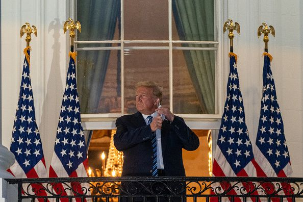 Trump, in a black suit and blue-striped tie, takes a mask off, standing with a black balcony railing in front of him and several US flags flanking him.