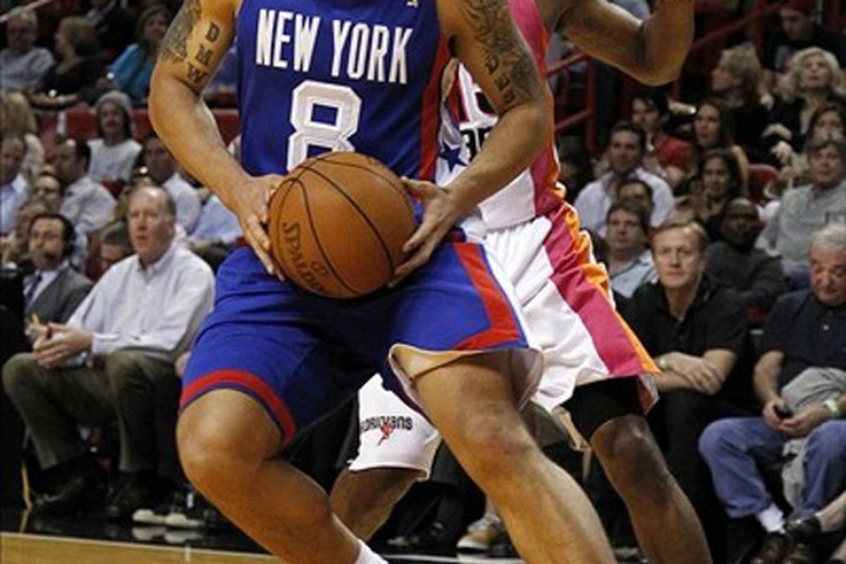 March 6, 2012; Miami, FL, USA; New Jersey Nets point guard Deron Williams (8) drives to the basket past Miami Heat point guard Mario Chalmers (15) in the first quarter at the American Airlines Arena. Mandatory Credit: Robert Mayer-US PRESSWIRE