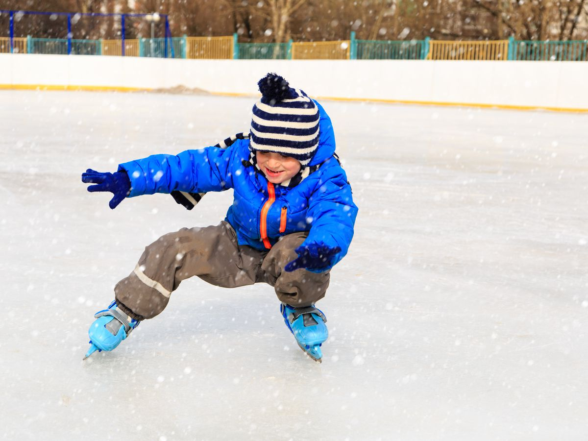A child is ice-skating in a rink. He has a blue jacket and a striped hat.