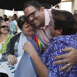 Gregory Enke hugs Terri Henry, right, and Penny Kirby, center, during a same sex marriage celebration at Library Square in Salt Lake City, Monday, Oct. 6, 2014.