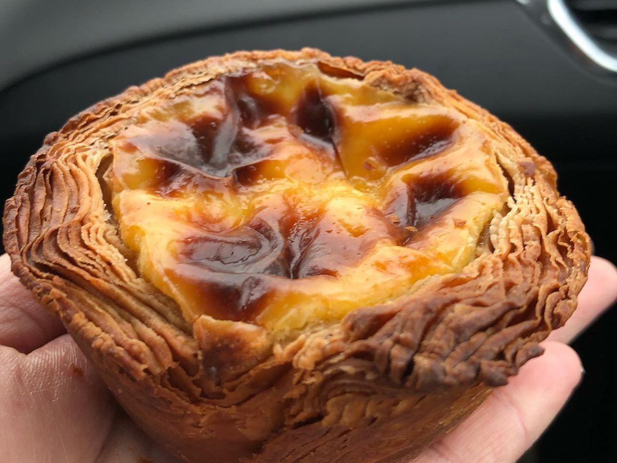 A hand holding an egg custard tart in a car