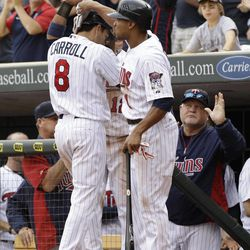 Minnesota Twins' Jamey Carroll, left, is greeted by teammate Ben Revere after scoring on a single by Pedro Florimon in the seventh inning of a baseball game Sunday, Sept. 30, 2012 in Minneapolis. At right is manager Ron Gardenhire. The Tigers won 2-1.