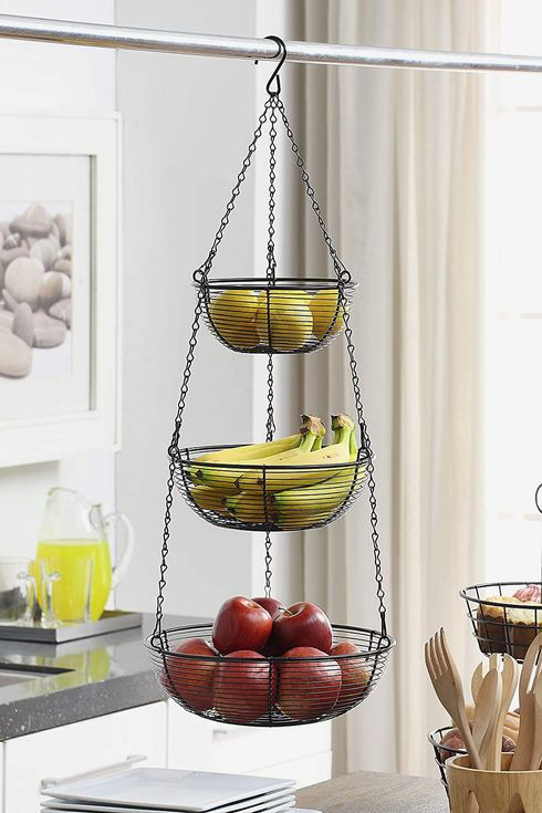 A three-tiered wire hanging basket filled with lemons, bananas, and apples